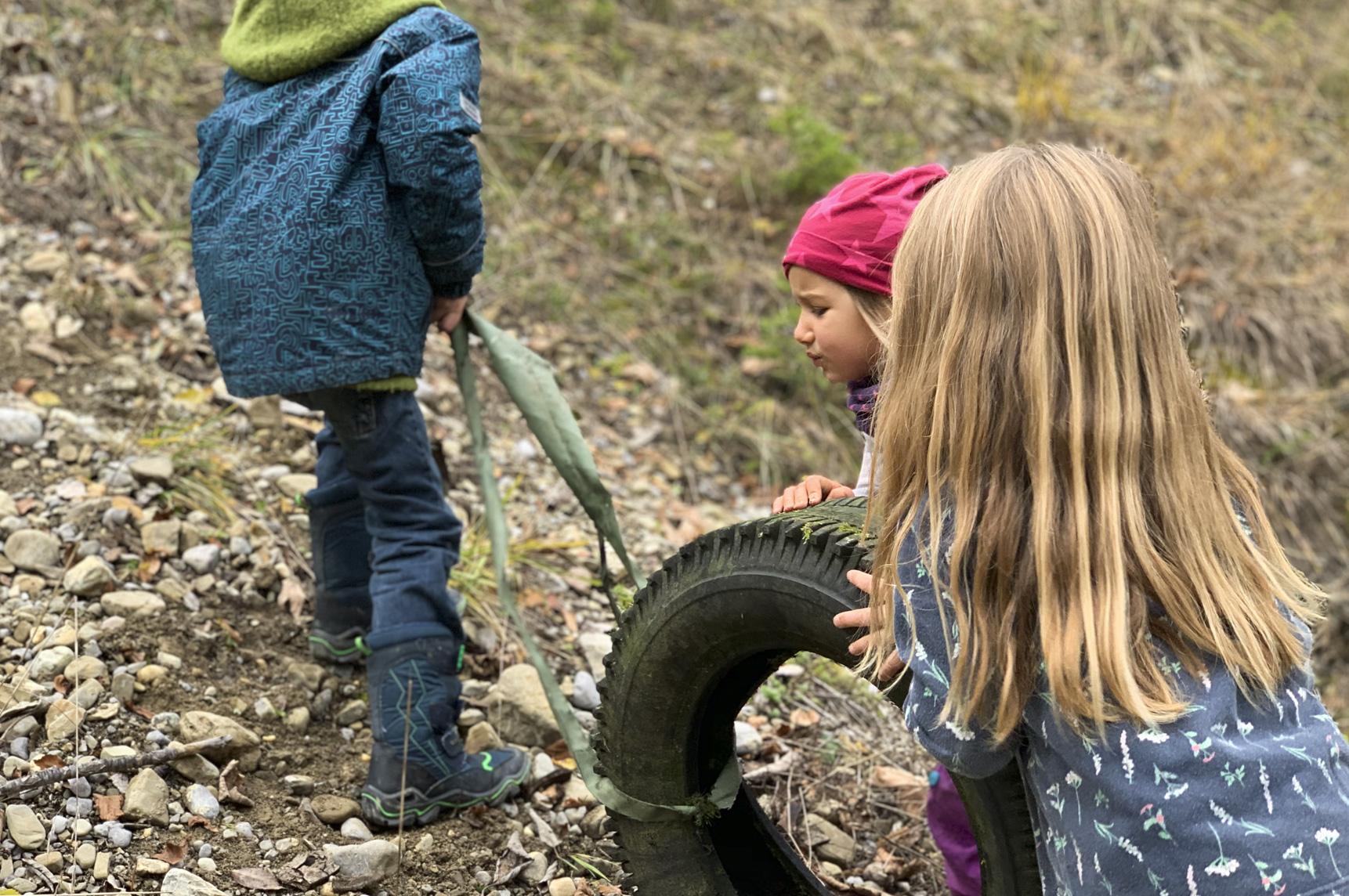 glückliche Kinder spielen mit einem alten Reifen